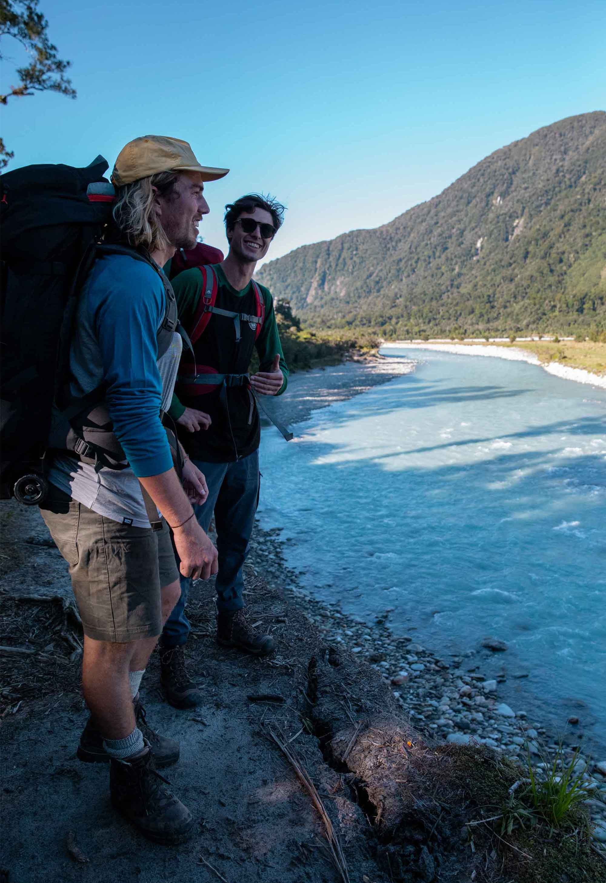 Hikers look over the river on the Copland Track in New Zealand