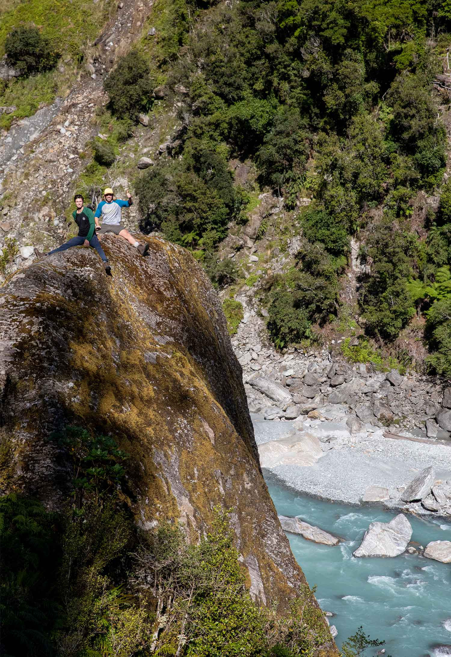 Hikers sit on a boulder on the Copland Track in New Zealand