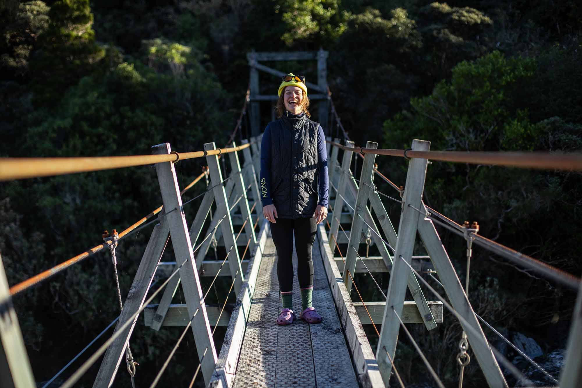 Female hiker on a bridge on the Copland Track in New Zealand