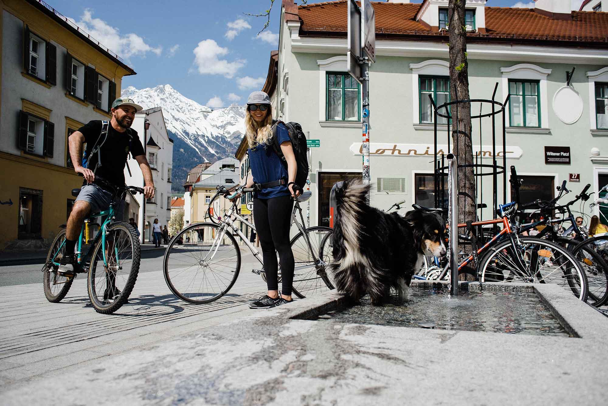 A man and woman walk a dog in Innsbruck, Austria